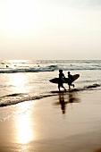 Kids running with surf board on beach, Indian Ocean, Hikkaduwa, Sri Lanka