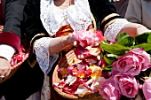 Close-up of woman holding basket of roses, Sardinia, Italy