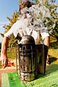 Beekeeper standing in front of beehive smoker, Kassel, Hesse, Germany