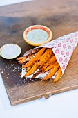 Sweet potato chips in a paper bag with herb sauce