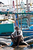 Senior man sitting on harbour with fishing boats in background in Tangalle, Sri Lanka
