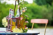 Bottles of syrup in a metal bottle basket on a garden table