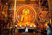 View of people visiting at sitting Buddha sculpture in temples, Colombo, Sri Lanka