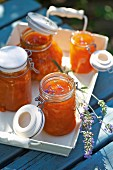 Jars of apricots jam on a tray outside