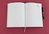 weißes Notizbuch mit Lesebändchen, Eselsohr, Kugelschreiber