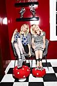 zwei Frauen sitzen in schrillen Partyoutfits auf Stühlen