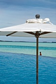 Parasol at swimming pool in front of sea, Dhigufinolhu island, Maldives