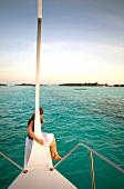 View of woman on boat and island Veliganduhuraa, Maldives