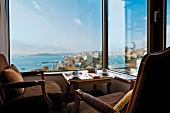 Chairs and table in front of widow overlooking cityscape and sea in Istanbul, Turkey