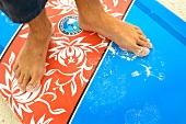 Close-up of man's feet on surfing board in Dhigufinolhu island, Maldives