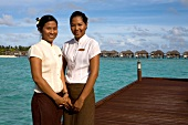 Two women standing on deck and Dhigufinolhu bungalows in water at dock in Maldives island