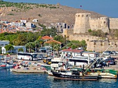 View of fishing boat at harbor and castle in Bozacaada, Turkey