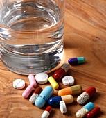 viele bunte Tabletten neben einem Wasserglas
