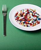 Tablettenmix auf einem Teller, Gabel, grüner Untergrund