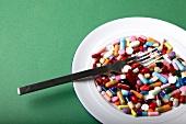 viele bunte Tabletten auf einem Teller, Gabel, grüner Untergrund