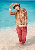 Frau steht im Meer und lächelt, trägt einen Hut, Strand, Wasser