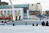 People at Place des Festivals with glass buildings in Quartier Latin, Montreal, Canada