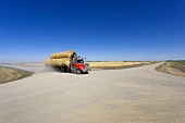 View of truck crossing the road 731 with bales of straw on road, Saskatchewan, Canada