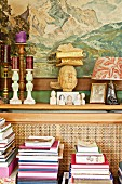 Collection of objet d'art on narrow shelf below painting of mountain landscape