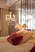Bed and chandelier in bedroom of hotel in Oslo, Norway