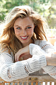 Portrait of pretty blonde woman wearing white sweater sitting on wooden chair, smiling
