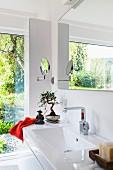 Helles Badezimmer mit Fensterfront, Waschtisch mit breiter Ablage & astiatischen Dekoobjekten
