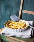 Potato gratin in a baking dish on a chair