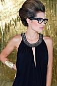 Frau mit toupierter Hochsteckfrisur, schulterfreies Abendkleid, Brille