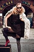 Frau posiert vor einer Bar in Kleid, Overknees, Booties, Vintage-Look