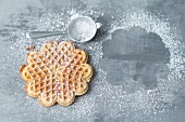A freshly baked waffle with icing sugar