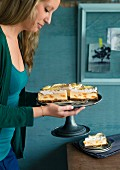 A woman holding a cake stand with Mandarin meringue cheesecake