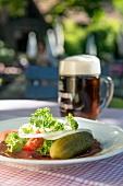 Brotzeit mit Schinken, Essiggurke & Bier auf Tisch im Freien