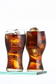 Two glasses of cola against a white background