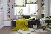 Als Tagesbett aufklappbarer Sessel mit Kissen und grün-gelber Strukturdecke an Fensterplatz zwischen Bücherregalen