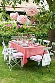 Gedeckter Tisch im Garten mit rosa Tischdecke & rosa Papierblütendeko