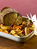 Roast beef with onions and vegetables in a roasting tin
