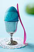 A blue Easter egg in an egg cup