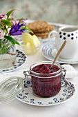 Boysenberry jam in a jar with crackers and butter