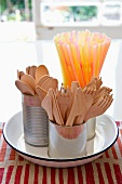 Wooden cutlery and straws in tin cups