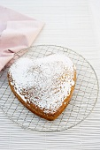 A heart shaped sponge cake dusted with icing sugar