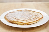 A pancake dusted with icing sugar