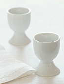 Two White Egg Cups with a White Napkin
