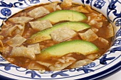 Bowl of Mexican Tortilla Soup with Avocado Slices