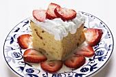Ein Stück Tres Leches Cake mit Schlagsahne und Erdbeeren