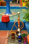 An oriental water pipe and glasses next to a fountain