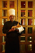 An Indian head chef serving naan bread