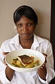Köchin serviert Seehecht mit neuen Kartoffeln, grünen Bohnen und Muschel-Safran-Sauce