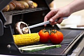 Vegetables and corn on the cob on a barbecue