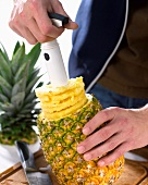 Pineapple slices being made with a pineapple cutter