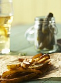Fries on Parchment Paper; Jar of Pickles; Glass of Beer